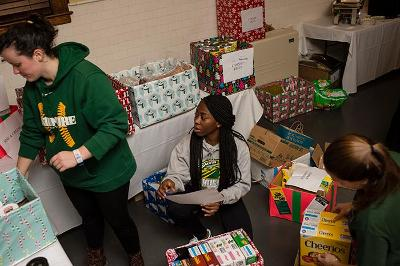 Students, including Gloria Ekeh '19, center, sort donations.