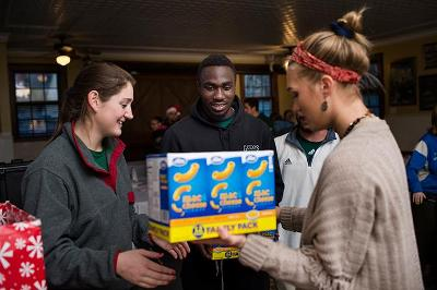 Students (including Adebare Oyeniyi '17, middle, and Madeline Kelly '19, right) sort donations.