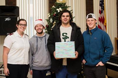 A Salvation Army staffer accepts donations delivered by Marc Cibelli '17, Christopher Javens '20 and Mickey Foley '18.