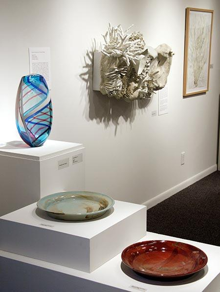 Installation view. Foreground, ceramic plates by student Megan Pini, demonstrating color changes using different glazes. Pini writes, 'The glaze aesthetics that viewers take for granted rely on chemical reactions and transformations. A thorough and intentional artist works to understand how these chemical reactions affect the final product, and...calculates a formula that benefits his or her work.' At left, glass vase by alumna Dorothy Hafner, who uses glass as a medium rather than ceramic in order to achieve the greatest brilliance of glaze color. On wall toward right, alumna Courtney Mattison's ceramic piece, Dissolve, inspired by her study of marine biology.