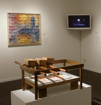 Installation view. Professor Sangwook Lee's Inkjet Printer in foreground. Background at left, student Michelle Molokotos's Representation of Monet's House of Parliament, made of paint tubes. Molokotos writes, 'My art is a statement on the impact of the paint tube on the development of Impressionist painting.' Background right, video by student Rivkah Gevinson.