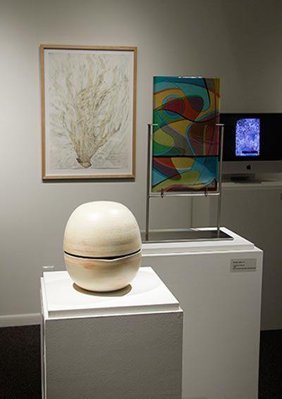Installation view. In foreground, untitled piece in wood-fired porcelain by alum David Kaufmann. In background, left to right: alumna Christine Neill's Toxic Beauty White Coral, an inkjet print & watercolor on paper; alumna Dorothy Hafner's Tangerine Crescent, fused glass and stainless steel; and, far right on monitor, part of Geosciences Professor Amy Frappier's display of thin sections of calcite seen in polarized light.