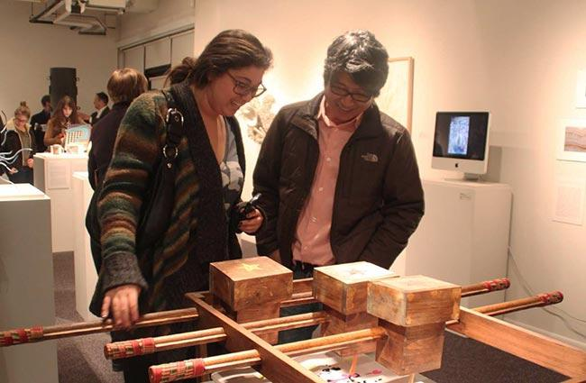 Professor Sangwook Lee and a student use the interactive inkjet 'copier' he built. Lee says, 'The idea for this piece came from my research on textile printers. Many machines seem very complicated. However, beneath the surface is a simple technology and idea.... I created this piece to show people that the printer is a simple machine at heart.'