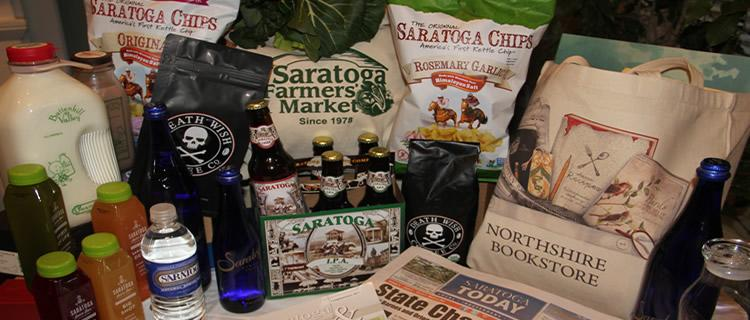 A sampling of SSCP Client Products: (left to right) Saratoga Juice Bar, Battenkill Creamery, Saratoga Chips, Death Wish Coffee, Saratoga Spring Water, Saratoga Farmers' Market, Saratoga IPA and Saratoga Lager, Northshire Bookstore. Saratoga Today Newspaper and Magazines, Roosevelt Baths and Spa.