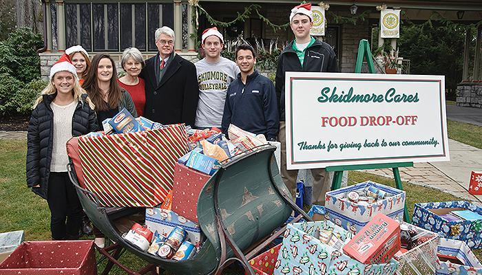 A group of 2014 volunteers stands with the sleigh of donations