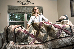 Elisa Smith '18 makes a bed at the Joan Nicole Prince Home. (Photo by Erin Covey)
