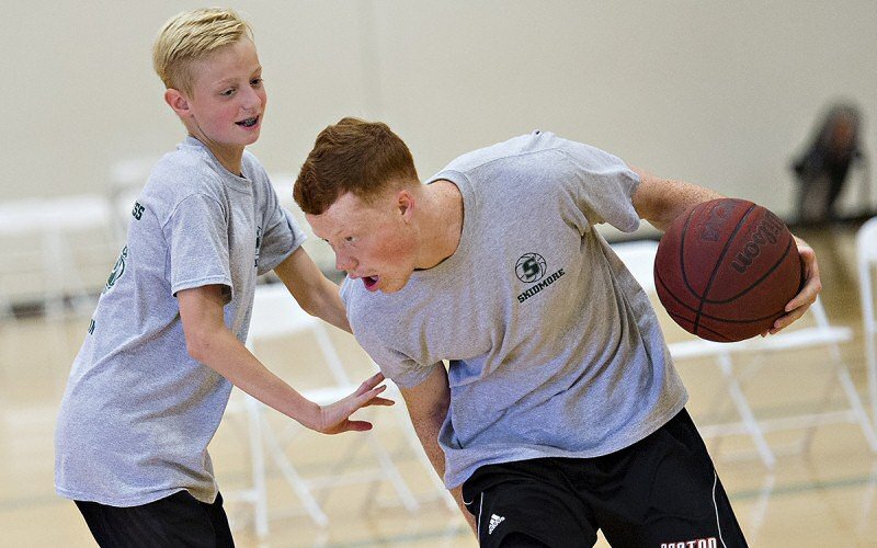 T'bred Pat Gallagher '20 (at right) shares some big moves with a young athlete during a hoops camp for sixth- through eighth-graders.