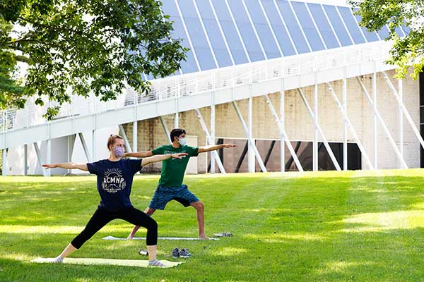 Two students perform yoga in front of the Tang Museuem