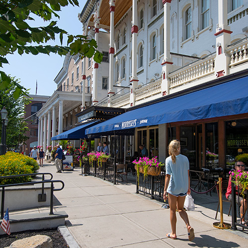 Woman walking down streets of Downtown Saratoga Springs looking into shops