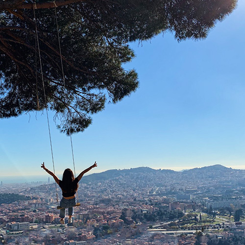 woman on a tree swing overlooking a city