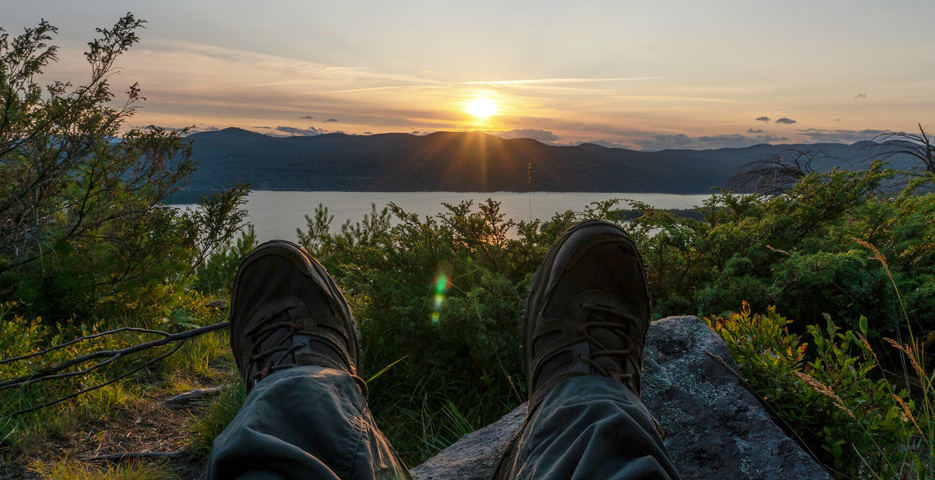 View of a sunset over a mountain from a hiker's perspective