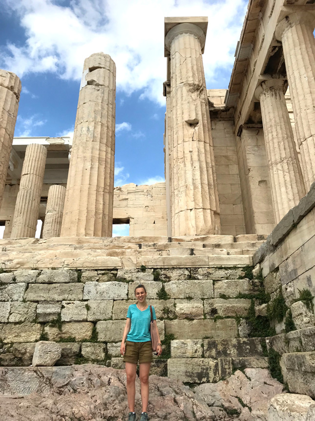 A college student stands in front of the Pantheon in Greece
