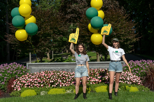 Two student stand by the Skidmore welcome sign