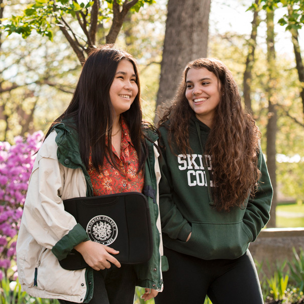 Two students walk on a college campus in the spring