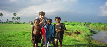 Skidmore student, Alex Tzelnic '07and kids outside a nearby school in Sujata Village