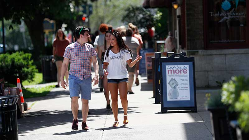 two people walk down busy downtown saratoga springs
