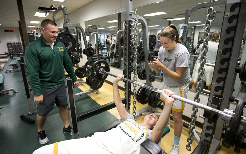 Matt Chatham oversees as two-time All-American Kelly Donnelly '18 works on bench presses, with Haley English '19 spotting.