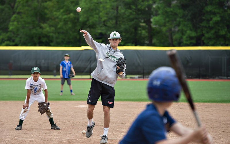 Thoroughbred pitcher Tim Allen '20 tosses to a young camper at bat during a baseball clinic for local 10-, 11-, and 12-year-olds.