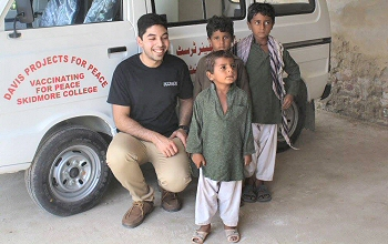 Ibrahim Shah '18 poses with local kids during his summer project to deliver vaccines in his home country of Pakistan.