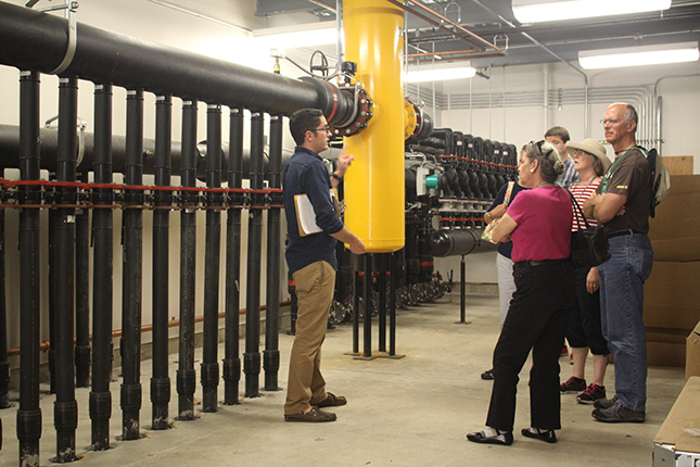 Levi Rogers gives campus visitors a tour of Skidmore geothermal system