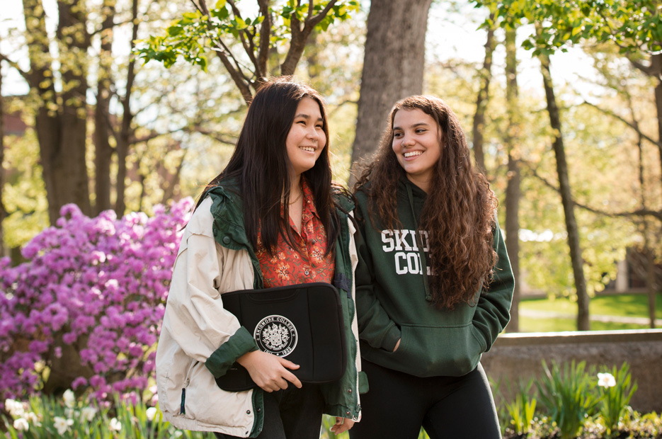 Two students walk on campus with spring flowers blooming in the background