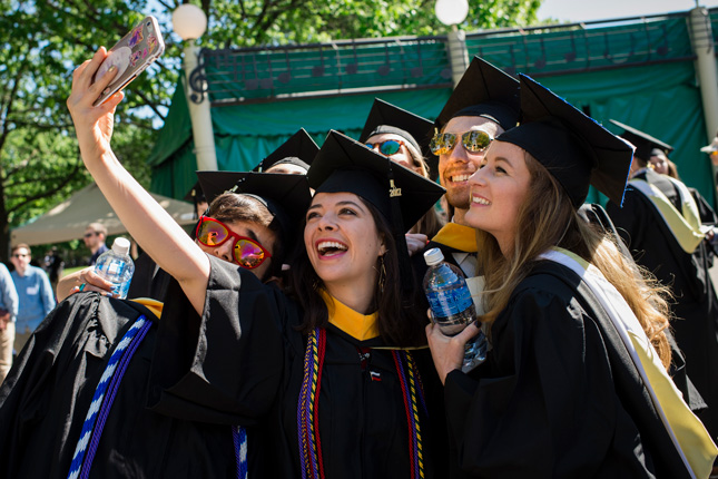 Student take a selfie in their gaps and gowns during commencement