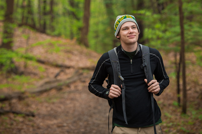 Student walking on a wooded trail