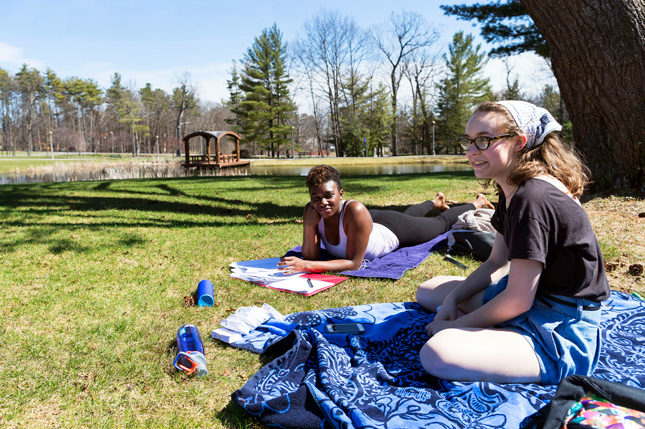 Two student sit by Haupt Pond