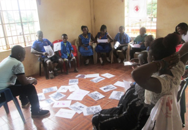 Student runs a meeting of people in a small room in Sierra Leone, Africa