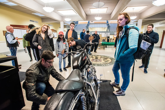 Student inspect a Harley Davidson motorcycle