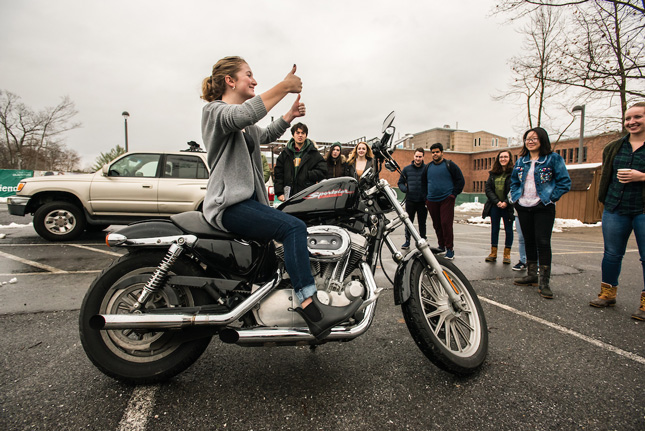 MB107 Students take turns behind the wheel of a harley-davidson motorcycle for research