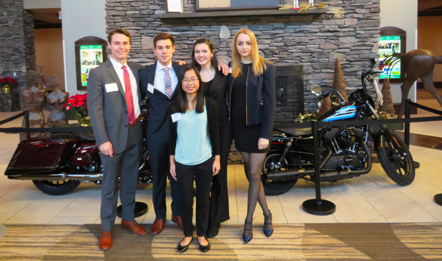 Members of an MB107 team pose in front of Harley-Davidson motorcycles in the lobby of the Embassy Suites hotel in Saratoga Springs following their executive presentation. Clockwise from left: Jack Leitner, '19 (coach), Spencer Bernard, '22, Alix DuBouloz, '22, Antonia Meade, '22, Grace Smith, '22.