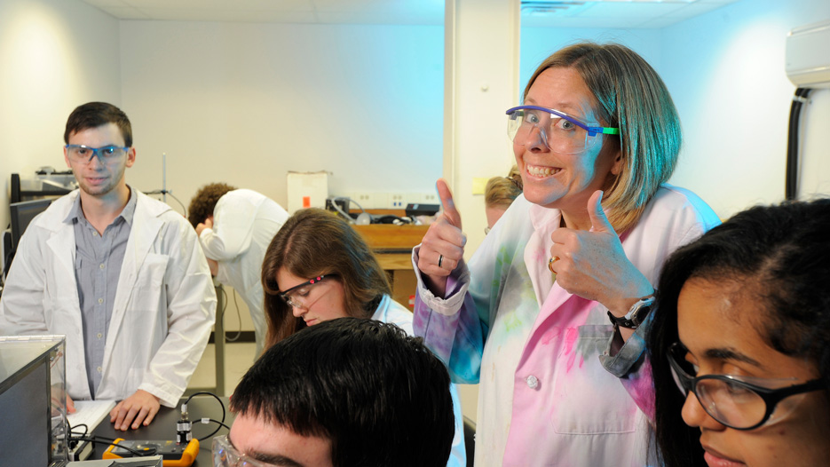 Kim Frederick, chemistry professor, gives two thumbs up in a laboratory