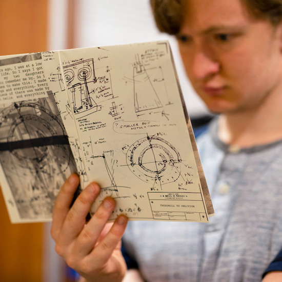 A+college+student+examines+a+book+filled+with+hand-drawn+engineering+diagrams+