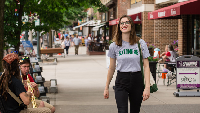 College student walking on a city street with a Skidmore t-shirt on