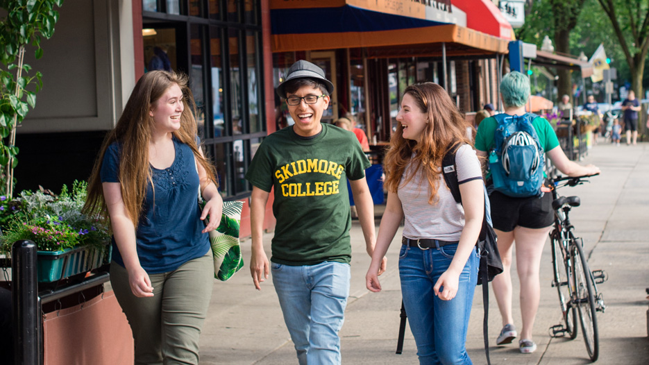 College students laughing as they walk on a city sidewalk