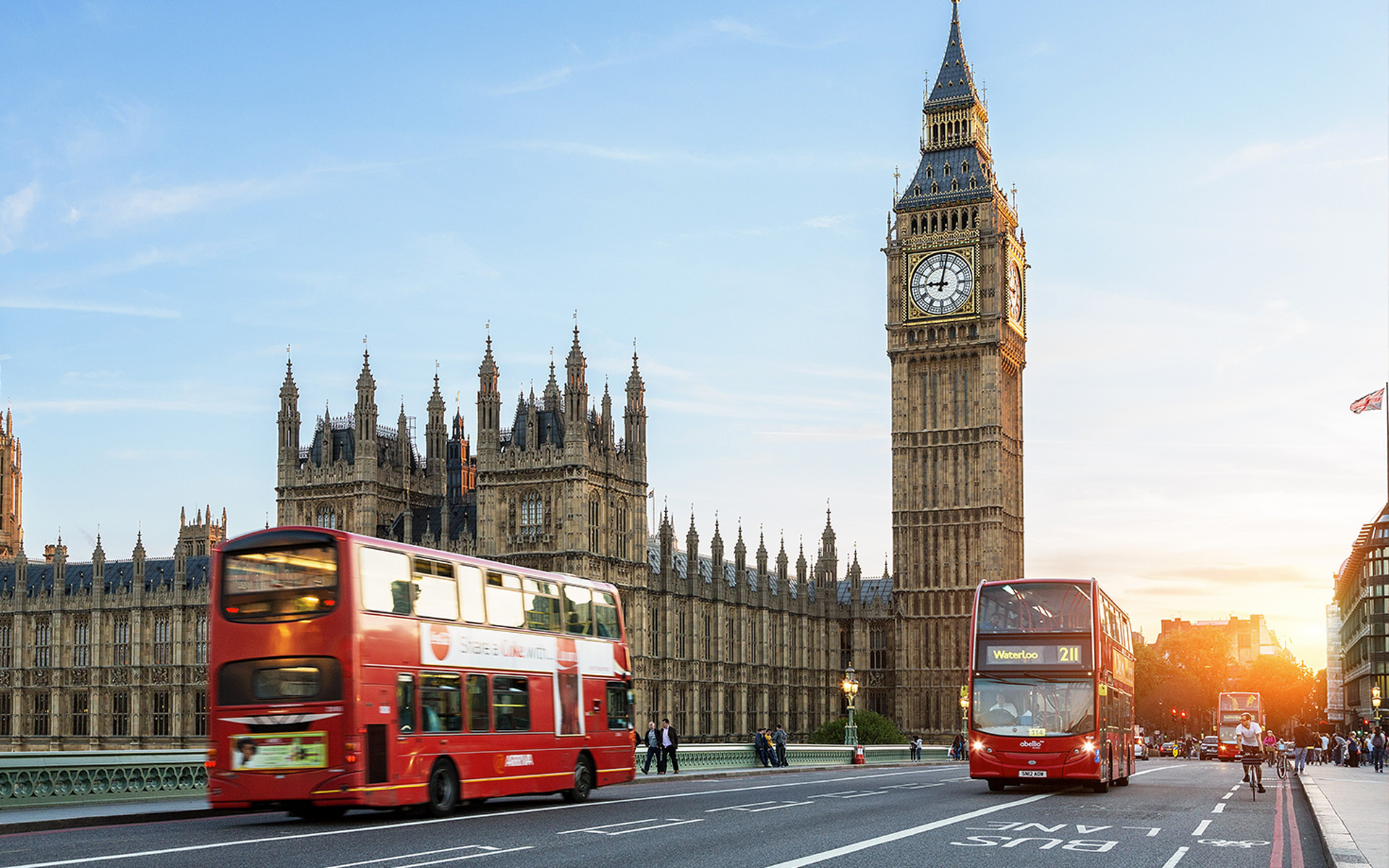 A double-decker bus driving by Big Ben in London, England