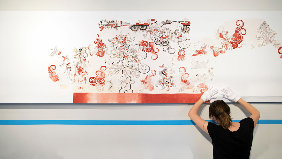 Heather Hurst hangs her watercolor paintings of a mayan temple mural