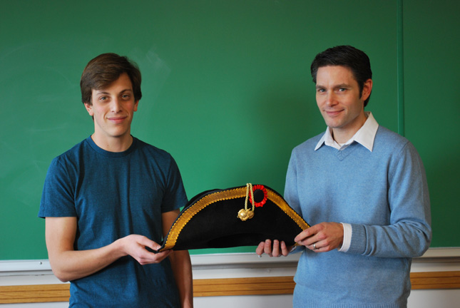 A student and professor pose with an 18th-century sailors hat