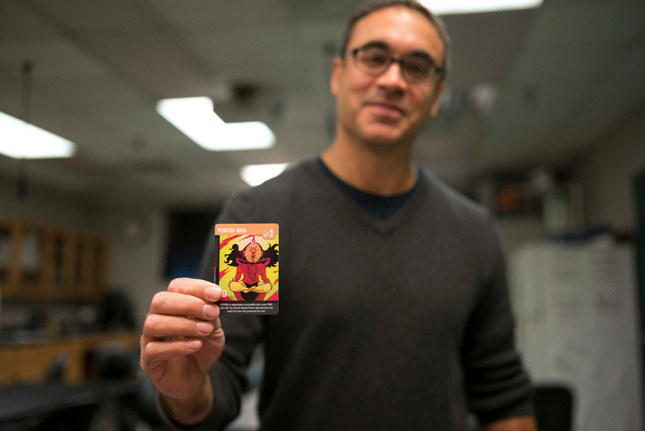 Hassan Lopez, professor at Skidmore, holds up a playing card from his board game
