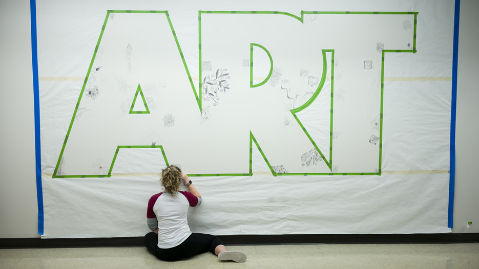 A student works on a mural during the Saisselin Art Center 40th Anniversary Celebration.