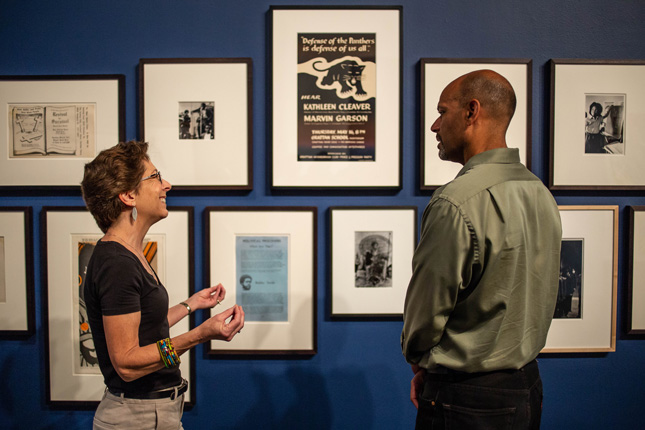 Adrienne Zuerner, Associate Professor of French, and Amon Emeka, Associate Professor of Sociology, discuss the collection of Black Panther objects in the exhibition Give a damn. Tang Teaching Museum photo.