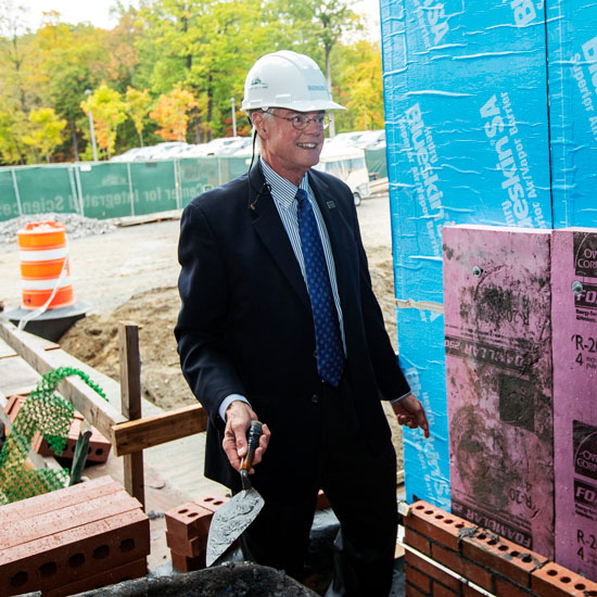President+Glotzbach+lays+brick+at+the+CIS+construction+site.+