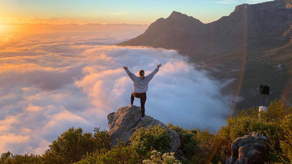A student studying abroad in South Africa has her photo taken overlooking a mountain range