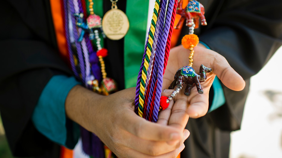 College graduate holds various colored regalia and cords in their hands