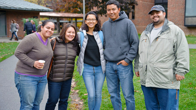 Skidmore student poses with their family on campus