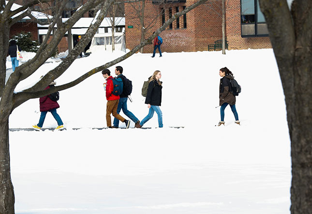 Students walk to and from classes on a snow-filled campus.