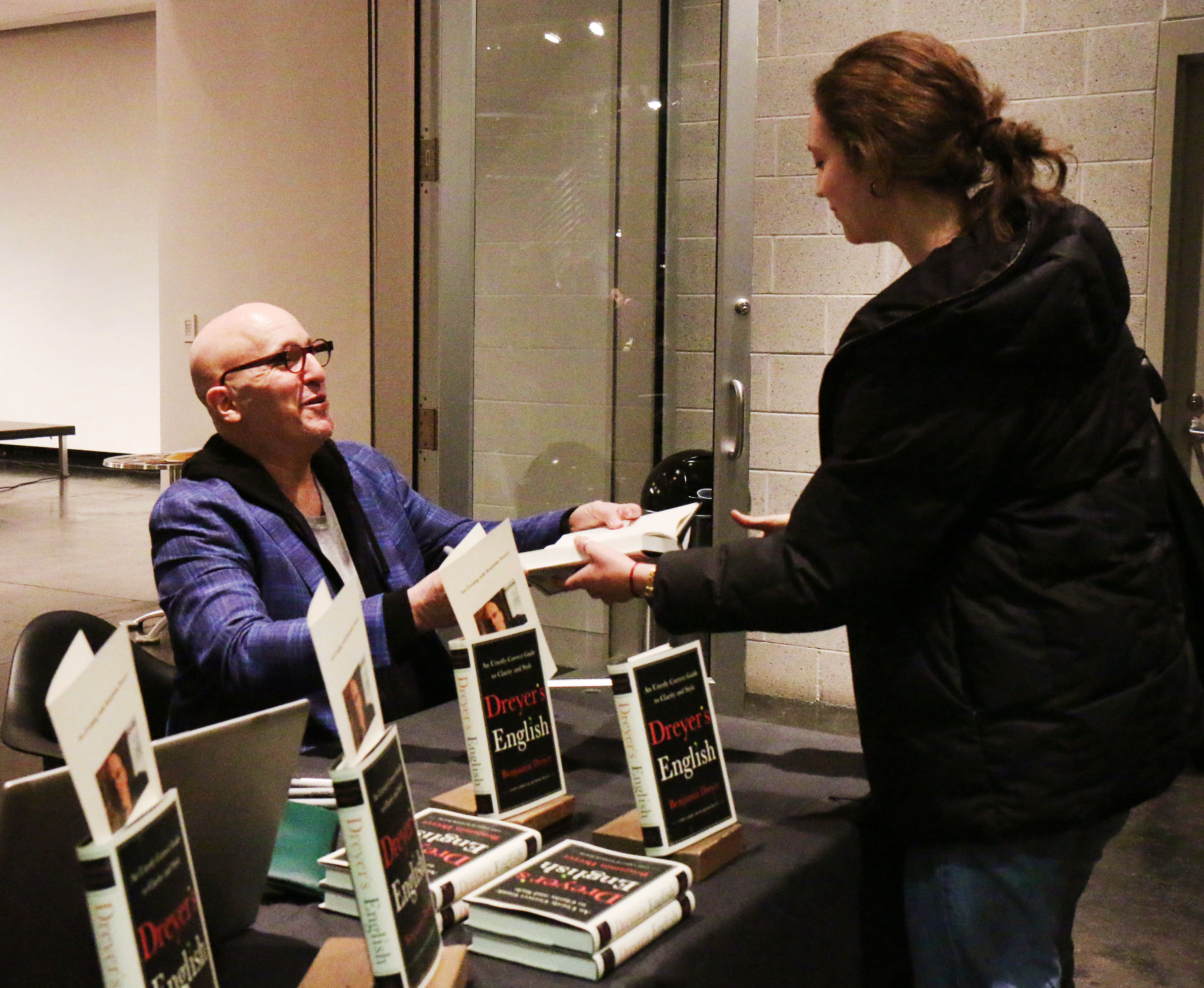 Dreyer signs copies of his book for students