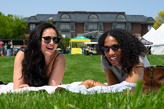 Two alumnae laying on lawn