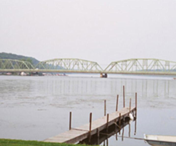 Boat dock on the water, with a bridge in the background
